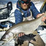Ice Fishing Guide Hunter Pierson with Gunnison Sports Outfitters landing a large lake trout at Blue Mesa Reservoir in Colorado.