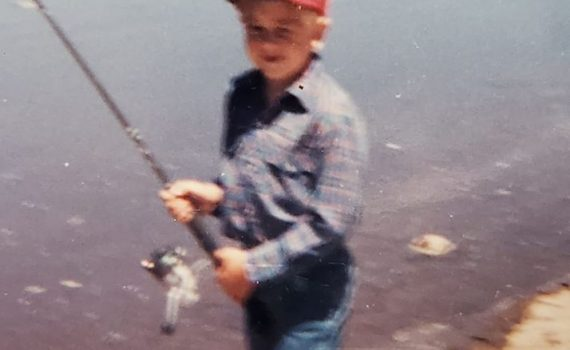 GSO Fishing owner Andy Cochran holding his fishing pole at the lakes edge when he was a child