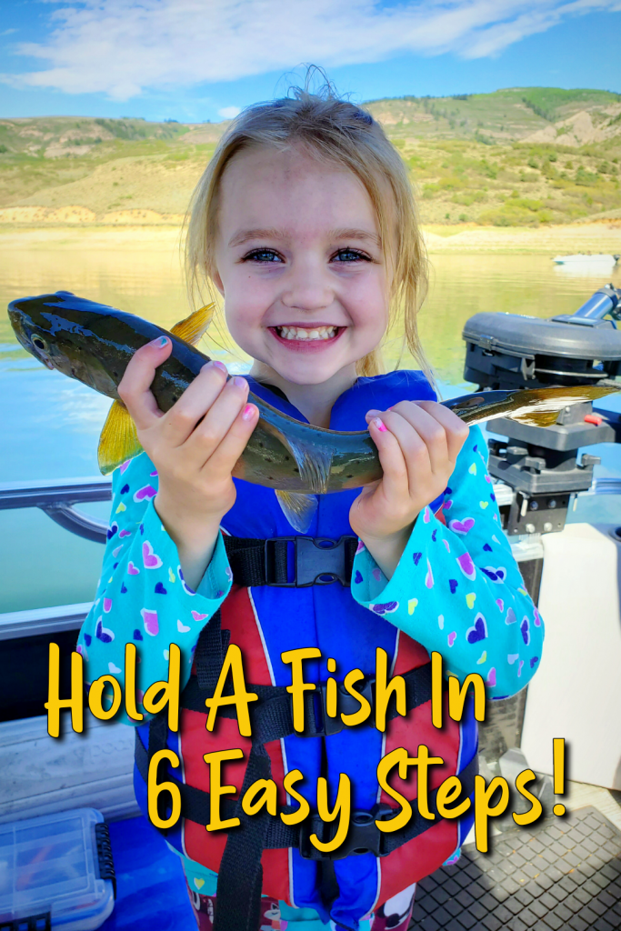 Hold A Fish: GSO Fishing Youth angler on their pontoon boat holding a brown trout at Blue Mesa Reservoir